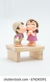 Closeup mini muñeca de plástico en beso romántico con fondo blanco.