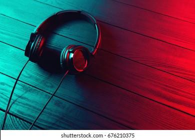 Black headphones on dark wooden background. Vintage style