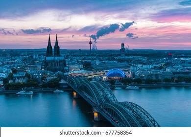Escena nocturna nocturna sobre la ciudad de Colonia / Koln con Kolner Dom / Catedral detrás del puente Hohenzollern y las torres de Koln, hermoso y colorido cielo al atardecer sobre el horizonte de Colonia
