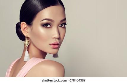 Asiatisches Modellmode-Mädchen mit Quastenohrringen und rosa Kleid.