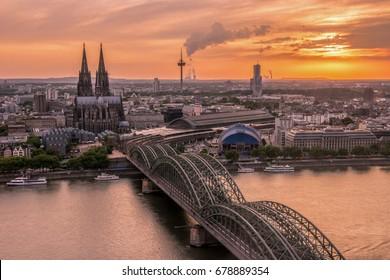 cielo del atardecer con colores y nubes sobre la ciudad de Colonia con el puente y la Colonia Dom, escena nocturna sobre la ciudad de Colonia / Colonia con la Catedral de Colonia / Catedral detrás del puente Hohenzollern y las torres de Colonia,