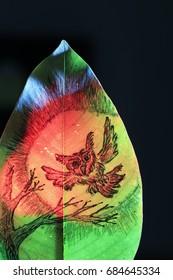 黒の背景に赤い光の緑の葉に月光の絵の上を飛んでいる赤いフクロウ