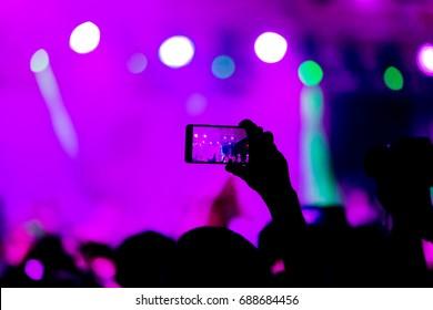 Fans genießen ein Konzert in der Fan-Zone der Halle während des Konzerts der Hamlet-Metal-Band Rammstein. Menschenmenge Silhouetten mit den Händen nach oben. Selektiver Fokus