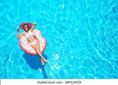 Schöne junge Frau mit aufblasbarem Donut im blauen Schwimmbad