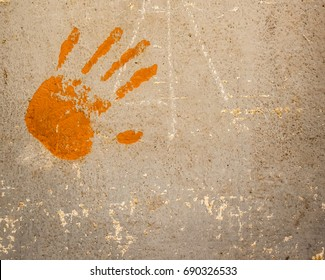 Human hand print in orange color on old plaster wall texture surface.