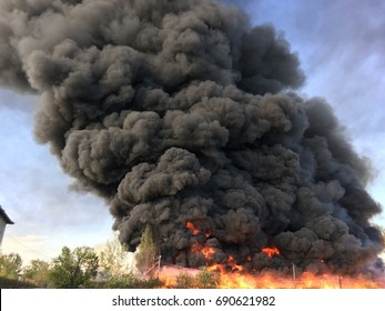 Warehouse engulfed in raging fire with huge column of smoke