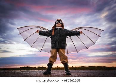 Niño con alas al atardecer se imagina a sí mismo como piloto y sueña con volar