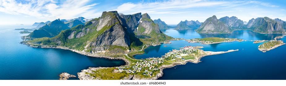 Luftpanoramablick des traditionellen Fischerdorfes Reine im Lofoten-Archipel in Nordnorwegen mit blauem Meer und Bergen während des sonnigen arktischen Sommers