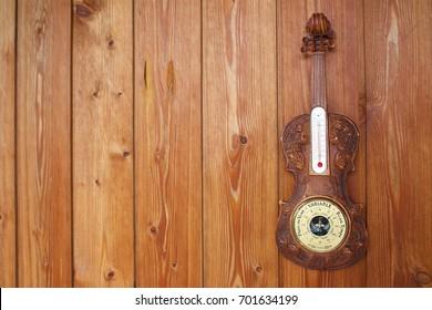 ビンテージバイオリン温度計と赤い水銀と木製の背景の気圧計