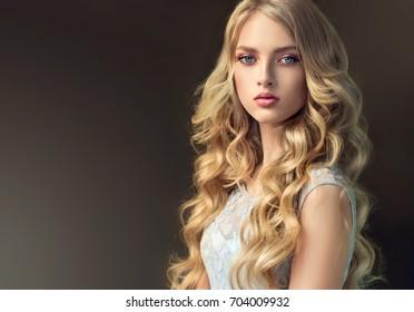 長くて光沢のある巻き毛のブロンドのファッションの女の子。ウェーブのかかった髪型の水色のドレスの美しいモデル。
