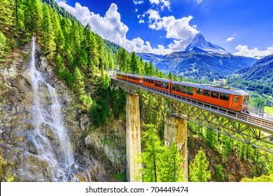 Zermatt, Suiza. Tren turístico Gornergrat con cascada, puente y Matterhorn. Región de Valais.