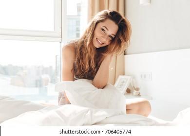 Positive Frau mit Kissen, das im Bett sitzt und zur Kamera zu Hause lächelt