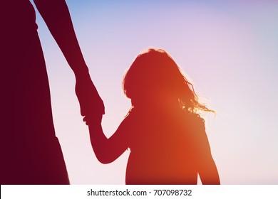 silueta de madre e hija cogidos de la mano al atardecer