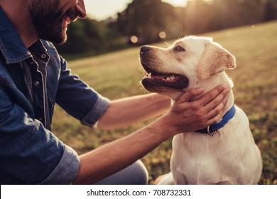 屋外でラブラドールとハンサムな若い男のトリミングされた画像。犬と緑の芝生の上の男。サイノロジスト