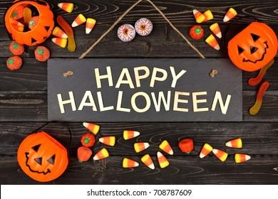 Feliz Halloween cartel negro con letras de madera y marco de caramelo sobre un fondo de madera negra