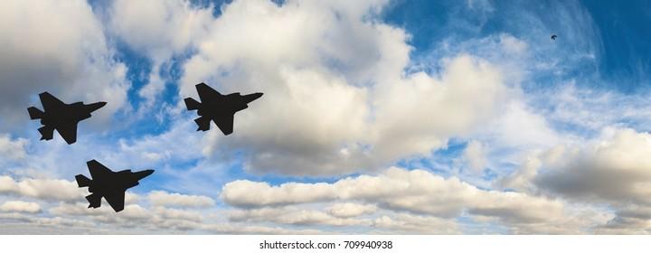 Siluetas de tres aviones F-35 contra el cielo azul y nubes blancas