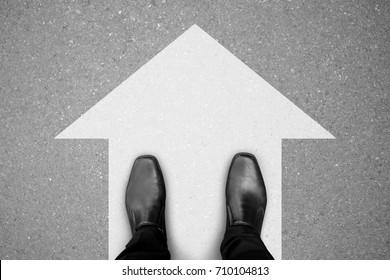 zapatos negros de pie sobre el piso de concreto asfáltico y señal de dirección blanca para seguir adelante.