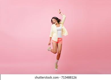 ピンクの背景に笑顔でジャンプの日焼けした肌を持つスリムな若い女性の全身像》。黄色のシャツ、ダンスと目を閉じて歌う幸せなブルネットの少女のスタジオポートレート。