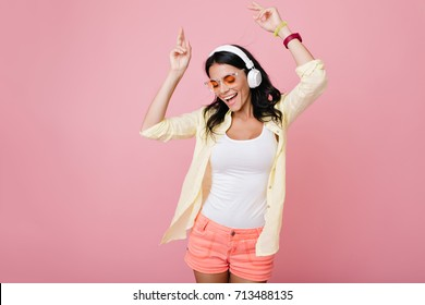 Inspired slim brunette girl in sunglasses funny dancing on pink background and waving hands. Laughing dark-haired young woman in yellow shirt enjoying music in headphones with eyes closed.