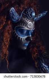 Fantastische sprookjesvrouw met blauwzwarte body-art, korset en hoorns
