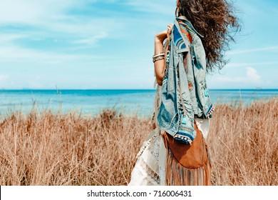 Cerca de la hermosa joven en vestido blanco en un campo