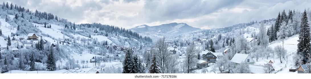 Panorama de la aldea en las montañas de invierno cubiertas de nieve. Paisaje de invierno. El concepto de libertad y soledad.