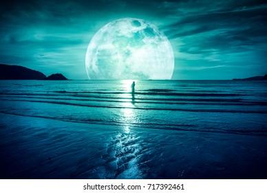 Supermond. Bunter Himmel mit hellem Vollmond über Seelandschaft und Schattenbild der Frau, die im Meer steht. Serenity Naturhintergrund, im Freien bei Dämmerung. Der Mond mit meiner eigenen Kamera aufgenommen.