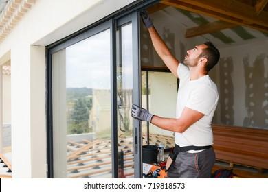 hübscher junger Mann, der Erkerfenster in einer neuen Hausbaustelle installiert