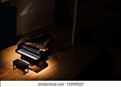 暗い部屋のスポットライトで黒いグランドピアノ