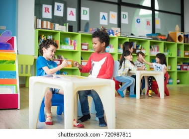 幼稚園のグループの子供幼稚園児が遊んでいて、教室でお絵かき科目を学ぶことに注目していて、一緒に学ぶことを楽しんでいます