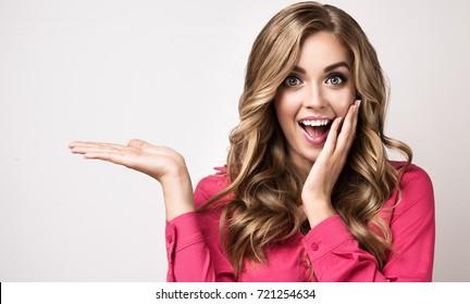 女性の驚きを示す製品。側を指している美しい少女。製品を紹介する。表情豊かな表情の感情実業家、