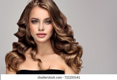 長而閃亮的捲發的黑髮女孩。捲髮髮型的美女模特女人。頭髮的護理和美容