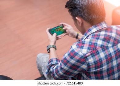La imagen abstracta del jugador asiático jugando videojuegos con el teléfono inteligente. el concepto de actividades, juegos, tecnología, estilo de vida, educación, e-sport e internet de las cosas.