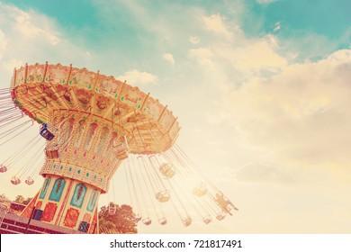 El carrusel gira rápidamente en el aire al atardecer - efectos de filtro vintage - un carrusel de balanceo en el parque de atracciones al atardecer