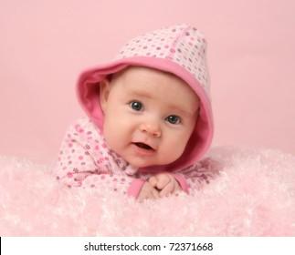 おなかの上に横たわるピンクの毛布と背景に愛らしい赤ちゃん女の子の肖像画