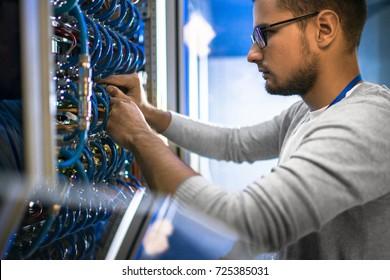 Retrato de vista lateral del joven con gafas conectando los cables en el gabinete del servidor mientras trabajaba con la supercomputadora en el centro de datos