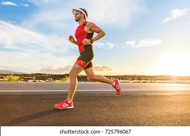 トライアスロン-アイアンマンレースのトライアスロンスーツトレーニングで走っているトライアスリートの男性。ハワイ島で運動する男性ランナー。日没。