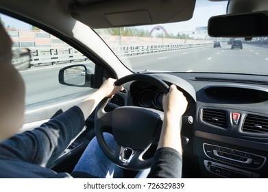 車を運転しながらハンドルを握っている女の子。