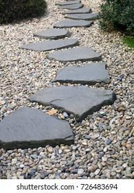 Pad van geplateerde stenen op grindbed in Japanse tuin. Meditatieve stenen loopbrug. Tuinarchitectuur, padaccessoire voor tuinvijver.