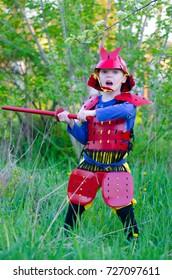 El joven samurái cosplay participa en la reconstrucción de la batalla en el bosque.
