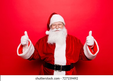 Have a holly jolly x mas! Festive seosonal occasion. Funny Saint Nicholas in red traditional outfit and head wear, isolated on red background, shows agree good gesture, wishing happiness