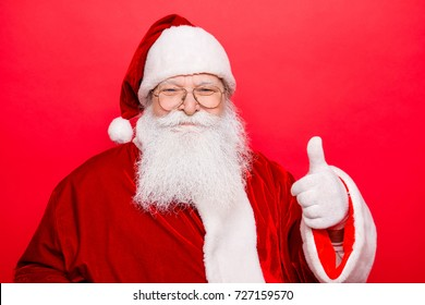 Who like to have presents and holly jolly x mas? Festive seosonal occasion. Funny Saint Nicholas in red traditional outfit, isolated on red background, shows agree good gesture, wishing happiness