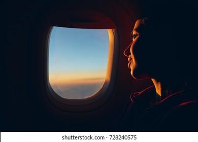 kadın bulutlar ile gökyüzüne uçak penceresinden bakıyor. 10.000 km yükseklikte günbatımı. kadının yüzü yakın çekim