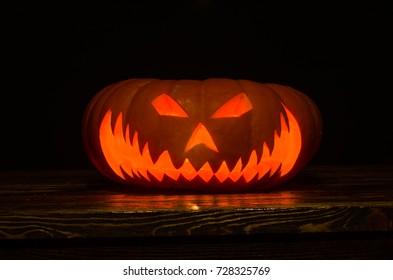 Beängstigende Halloween-Kürbisse mit den Augen, die innen am schwarzen Hintergrund leuchten