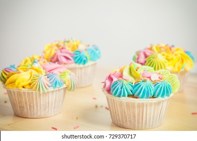 Four appetizing cupcake decorated with yellow, pink and blue pokemon and decorations on a table on a white background