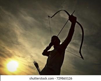 die Silhouette eines Bogenschützen mit Dämmerungshintergrund