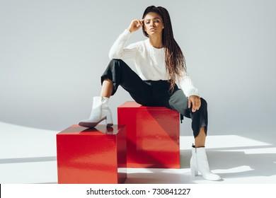 schöne modische junge Afroamerikanerfrau, die auf roten Würfeln sitzt und Kamera betrachtet