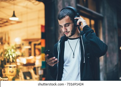 Hispanischer junger attraktiver Mann steht in der dunklen Straße vor Geschäft, ändert Lieder und Titel auf Smartphone, hört Musik in drahtlosen Kopfhörern. Hipster mit leichtem Bart