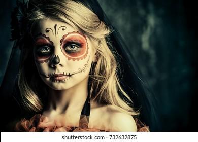 Retrato de una niña en un traje de Calavera Catrina sobre fondo oscuro grunge. Niña con maquillaje de calavera de azúcar. Fiesta de Halloween. Dia de los muertos. Dia de los Muertos.