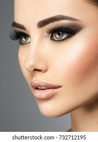 Closeup rostro de una bella mujer con pestañas largas. Retrato de una hermosa joven adulta. Señora atractiva atractiva que presenta en el estudio sobre fondo gris.
